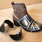 Here a solution how to affix the elements of a plate armor to shoes: attached D-rings and cords